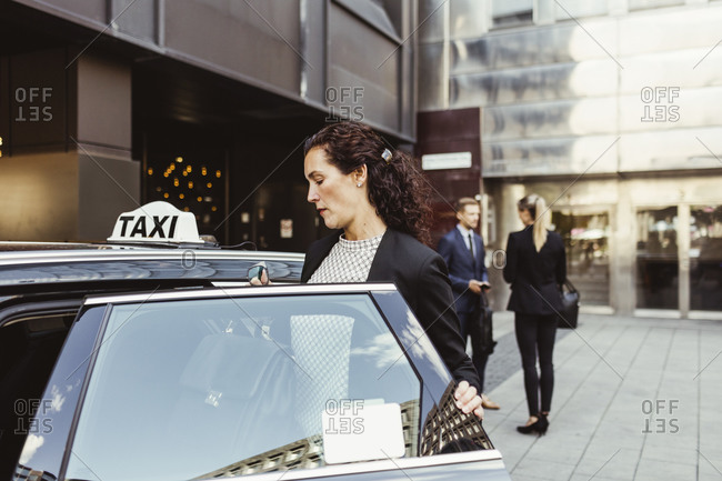 Female entrepreneur entering in taxi while coworkers standing in background