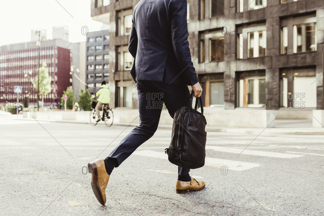 Low section of male entrepreneur with bag crossing street
