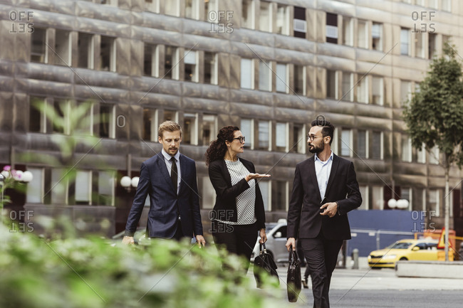 Female entrepreneur discussing business strategy with male colleagues while walking outdoors