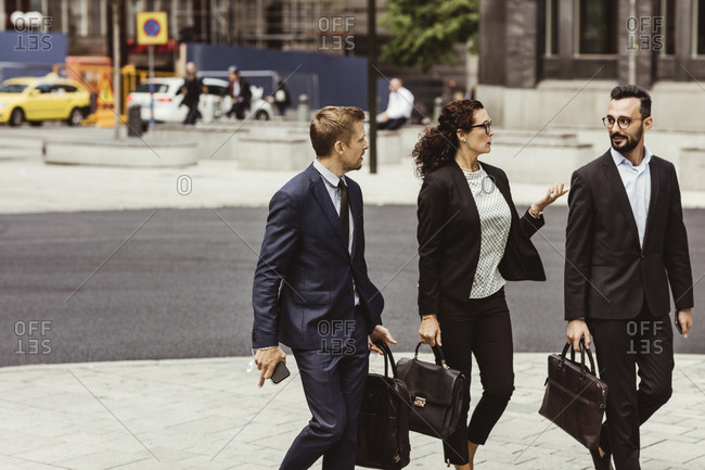 Female entrepreneur discussing business strategy with male coworkers while walking outdoors