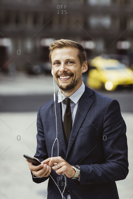Portrait of smiling entrepreneur using smart phone through in-ear headphones while standing outdoors
