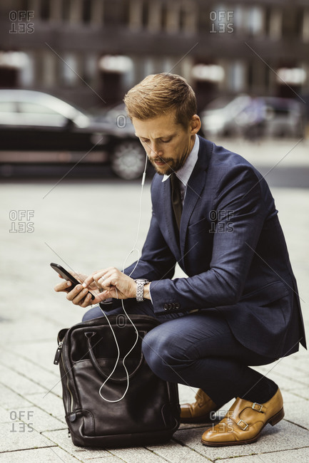 Male entrepreneur looking at time while crouching on street