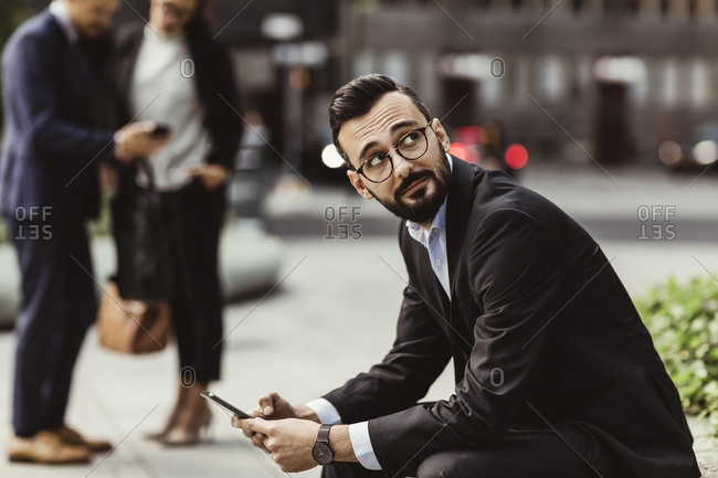 Businessman looking up while using mobile phone outdoors