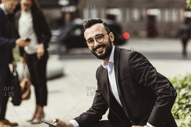 Portrait of smiling businessman with mobile phone sitting outdoors