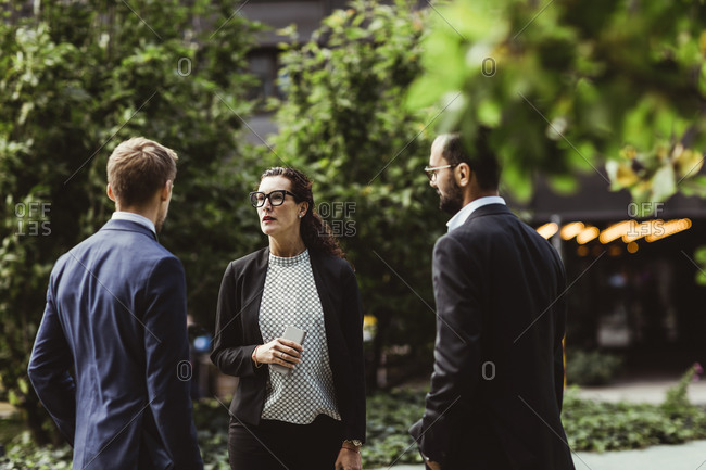 Female and male entrepreneurs discussing business strategy while standing outdoors