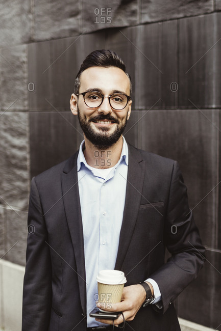 Portrait of confident businessman with disposable cup standing against wall