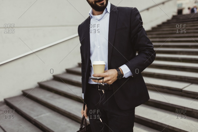 Midsection of businessman with disposable cup and smart phone standing on staircase