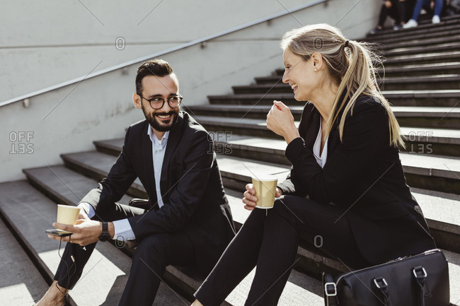 Smiling business people with coffee sitting on staircase