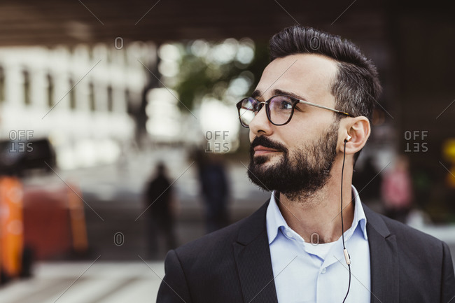 Confident businessman with in-ear headphones looking away while standing outdoors