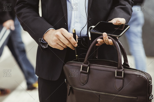 Midsection of male business person putting pen in bag while standing outdoors