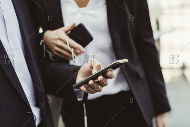 Midsection of business professional using smart phone while standing with female colleague outdoors