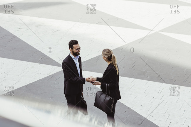 High angle view of business people shaking hands while standing on street