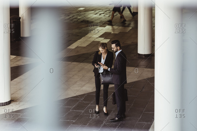 High angle view of business people using phone while standing on street