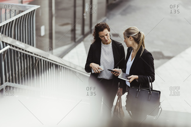 Businesswoman showing smart phone to female colleague while discussing on steps