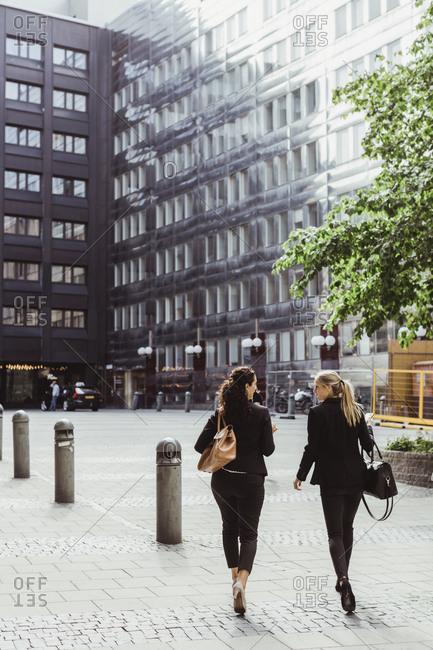 Rear view of female entrepreneurs walking on footpath