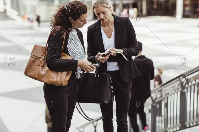 Businesswoman showing smart phone to female colleague while standing outdoors