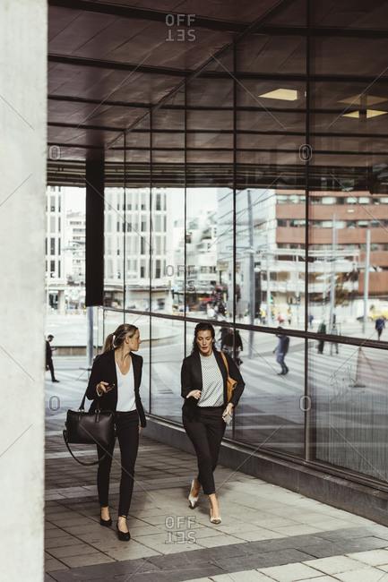 Businesswomen talking while walking on footpath