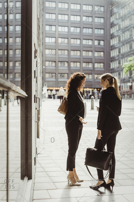 Businesswomen talking while standing by building