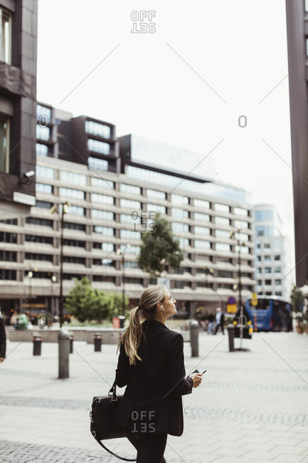 Female entrepreneur looking up while walking outdoors