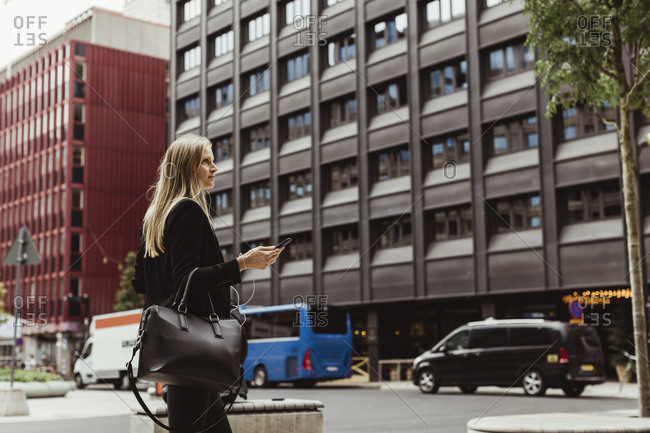 Female entrepreneur with smart phone walking against building