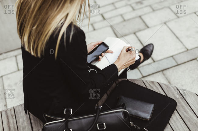 Low section of businesswoman writing while sitting outdoors