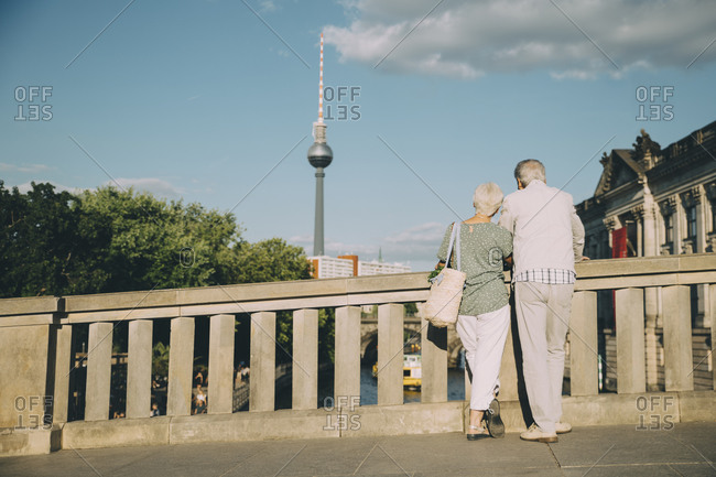 Rear view of senior couple looking at communications tower from bridge in city on sunny day