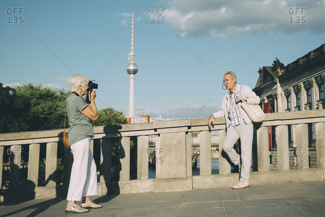 Full length of woman taking photograph of senior man while standing on bridge against tower in city