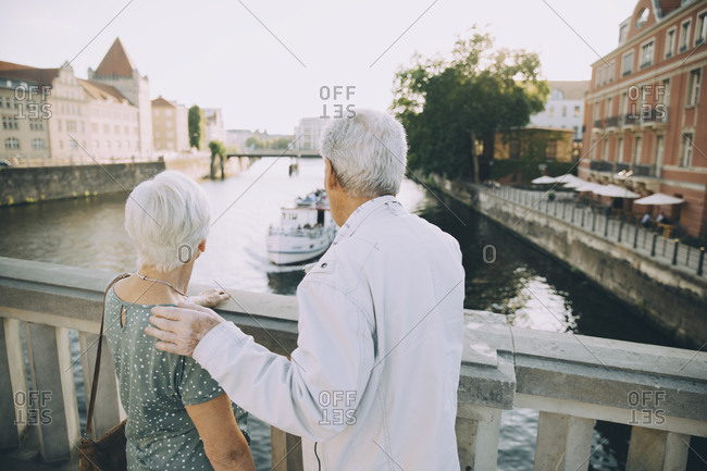 Rear view of senior couple standing on bridge against railing in city