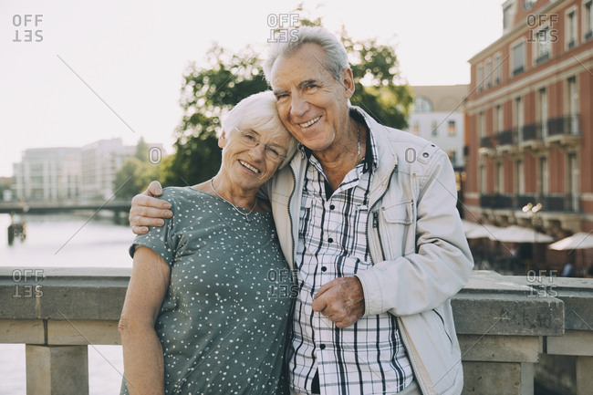 Portrait of smiling senior man arm around standing with partner against railing in city