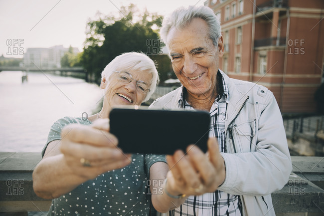 Smiling senior couple taking selfie with mobile phone while standing against railing in city