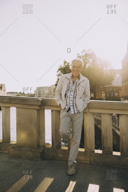 Full length portrait of senior man standing on bridge against railing in city