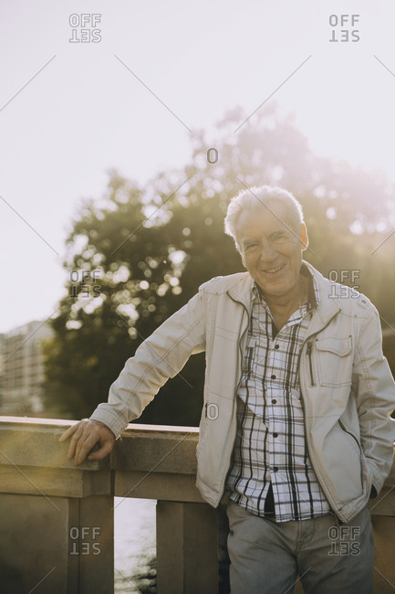 Portrait of smiling elderly man standing against railing in city on sunny day