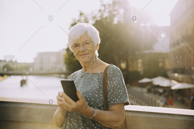 Portrait of senior woman holding mobile phone standing against railing in city