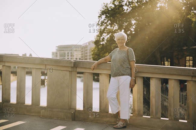 Full length portrait of senior woman standing on bridge against railing in city