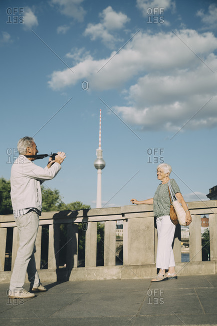 Full length of man taking photograph of senior woman while standing on bridge against tower in city