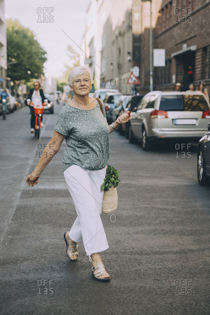 Full length portrait of woman walking on sidewalk in city