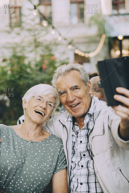Senior man taking selfie with happy woman while sitting at restaurant in city