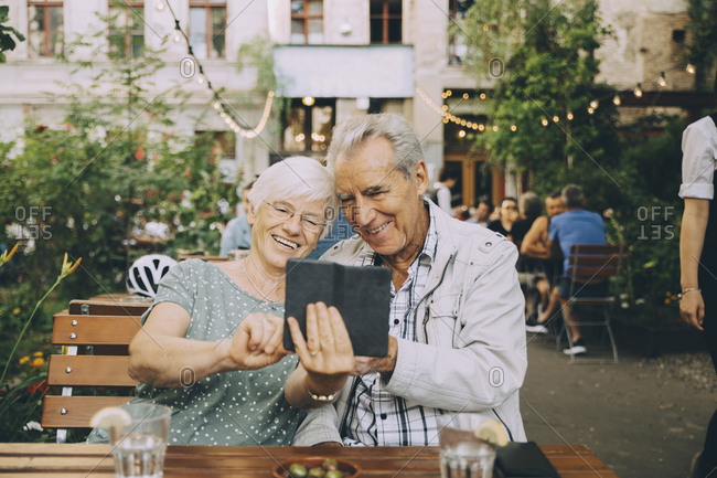 Smiling woman taking selfie with senior man while sitting at restaurant in city