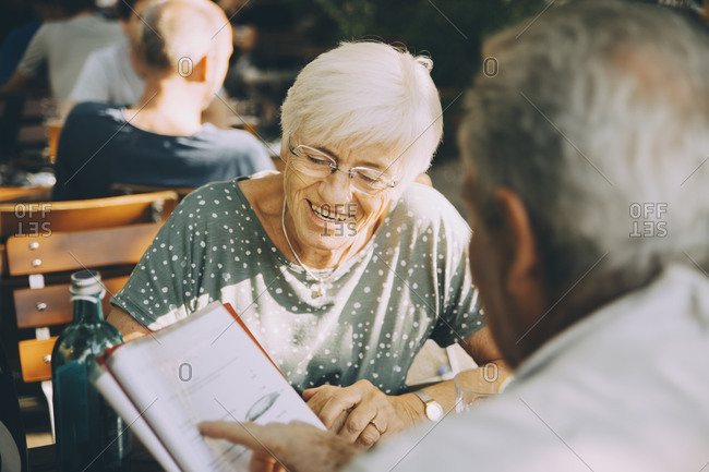 Senior couple tourist discussing menu while sitting at restaurant in city