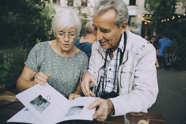 Senior man and woman tourist looking at pictures in book while sitting in restaurant
