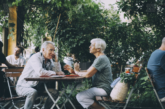 Elderly woman talking with man while sitting at restaurant in city