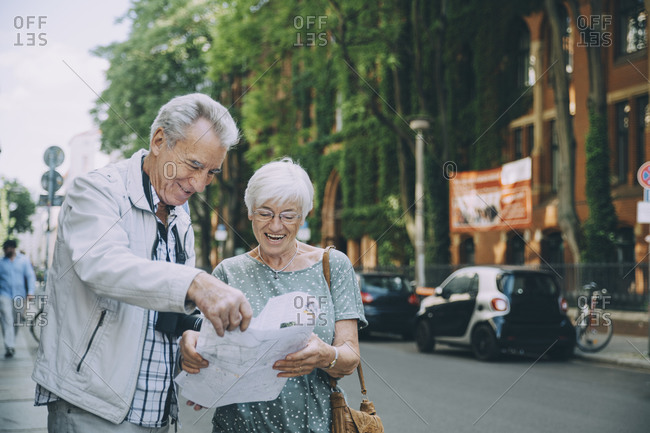 Smiling elderly couple reading map while standing on sidewalk in city during vacation