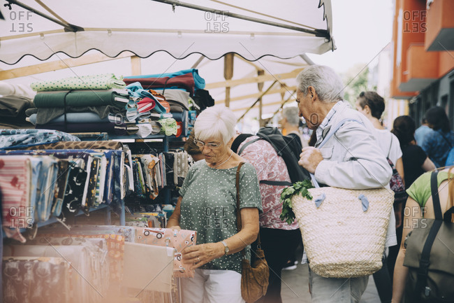 Male and female tourists shopping for textile at street market in city