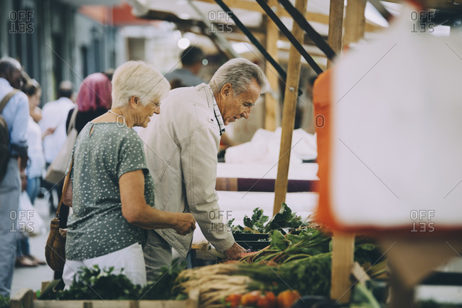 Senior male and females shopping for vegetables at market in city