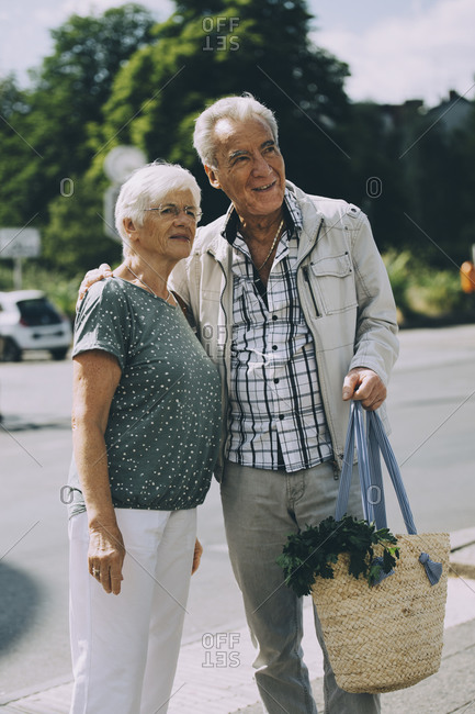 Elderly man arm around standing with woman on road in city