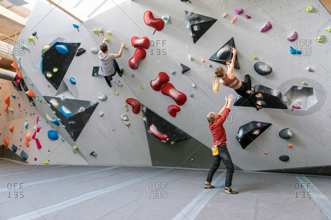 Male trainer training woman and man in wall climbing at gym