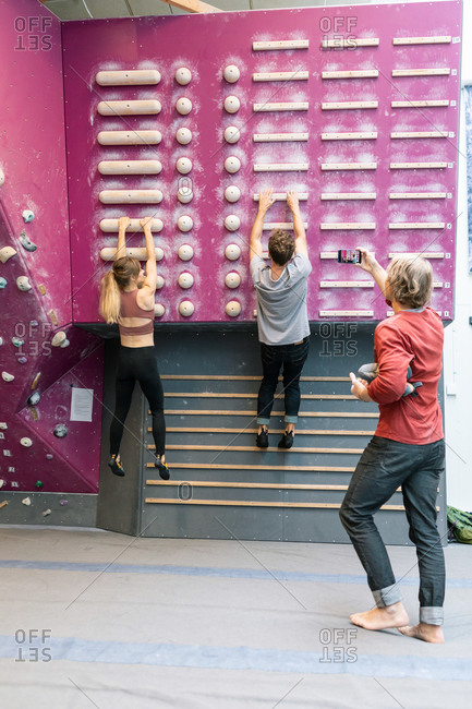 Male and female students practicing wall climbing while mature coach photographing in gym