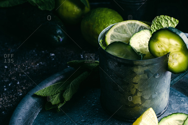 From above metal mug of cold cucumber detox drink with slices of lime and leaves of mint placed on tray
