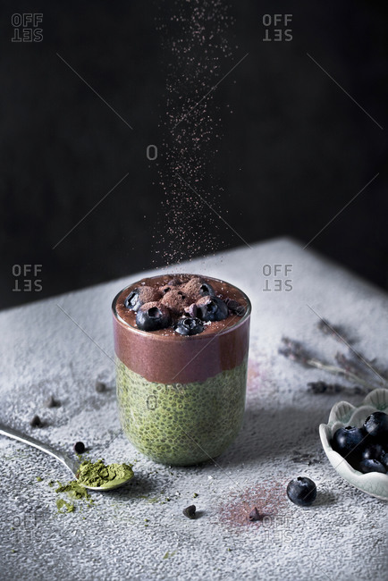 Glass of appetizing healthy matcha tea and chia seeds smoothie with chocolate and blueberries sprinkled with cocoa powder on dusted with sugar powder table