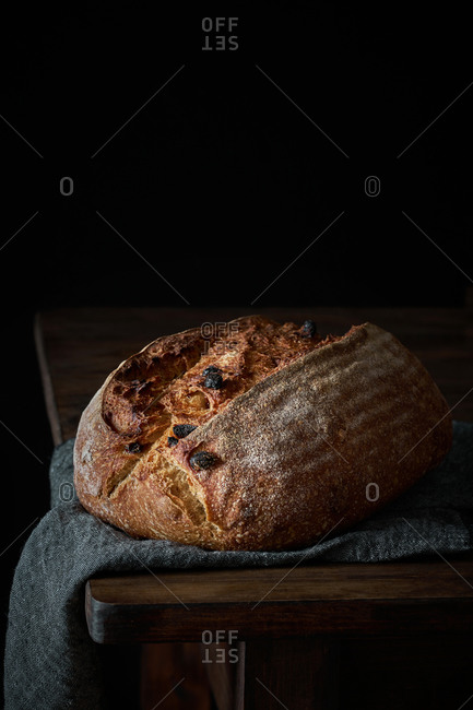 Crispy freshly baked sourdough bread loaf with raisin placed on gray cloth on wooden table with black background